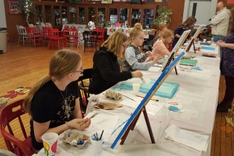 Kids learning to paint at birthday party