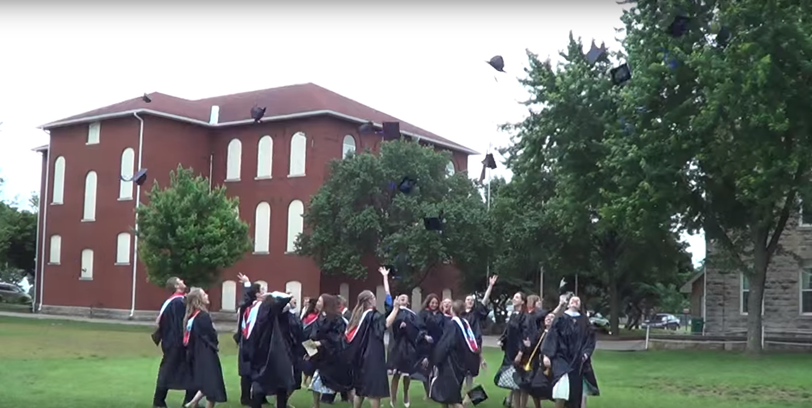 Students throwing their hats after graduating high school.